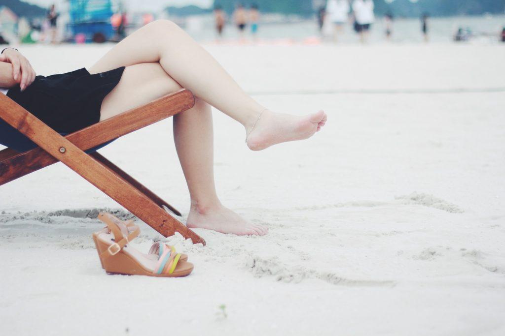 Una mujer tumbada en la hamaca descalza sobre la arena.