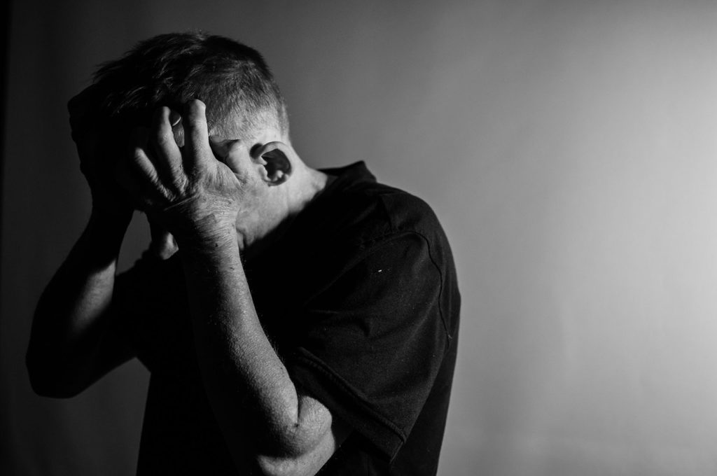 Un hombre deprimido se echa las manos a la cabeza tras una mala noticia.