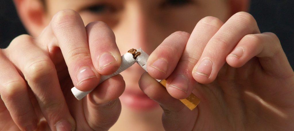 Niño partiendo un cigarrillo en señal de abandonar el mal hábito del tabaco.